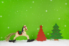 Rocking horse and red christmas tree on green background. Stock Photos