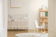 Rocking horse on rug in white kid`s bedroom interior with rabbit poster above cradle. Real photo stock photos