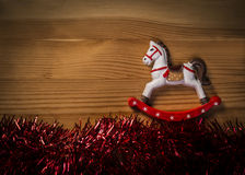 Rocking Horse Toy over wooden texture background with glossy garland Royalty Free Stock Images