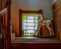 Rocking horse in the window. An antique rocking horse toy on the stairs landing Stock Photo