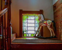 Rocking Horse In The Window. An antique rocking horse toy on the stairs landing Royalty Free Stock Images