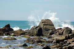 Rocking Waves. Photo taken in Florianopolis, Brazil of some waves crashing against some big rock formations, surrounded by other smaller rock formations Royalty Free Stock Image