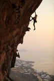 Rockklättrare på solnedgången Arkivbild