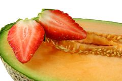 Rockmelon Strawberry. Halved strawberry on but rockmelon Stock Images