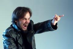 Rockmusiker, -fan oder -radfahrer Ein Kerl mit einem Bart in einer schwarzen Jacke schreiend und Daumen herauf Symbol zeigend ist stockbilder