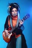 Rockowa dziewczyna matrycuje na gitarze elektrycznej na błękitnym tle Fotografia Royalty Free