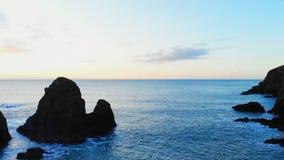 Rockowa formacja w morzu przy półmrokiem 4k zbiory