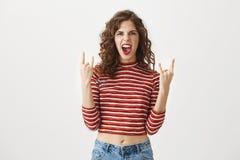 Rockowa n rolka jest żywa Budzący emocje figlarnie atrakcyjny żeński seans skały gest z oba ręki i krzyczeć od zdjęcia royalty free
