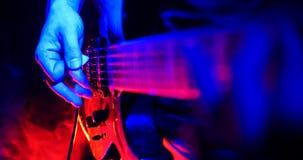 Rockowy koncert Gitarzysta bawić się gitarę Gitara iluminująca z jaskrawymi neonowymi światłami Ostrość na rękach zdjęcie royalty free