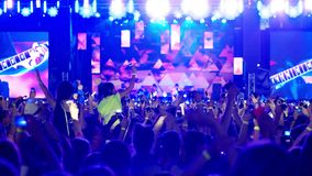 Rockowy koncert przy stadium udziałem tłum ludzie trzyma gadżety błyszczy na cenie, zbiory wideo