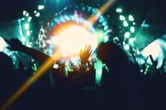 Rockowy koncert z sylwetek ludźmi w szczęśliwym gescie i rodzynce obraz stock