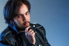 Rockowy stylu lub rowerzysty temat Portret czarnogłowy facet z brodą w czarnej skórzanej kurtce trzyma rękę na jego podbródku błę zdjęcia royalty free