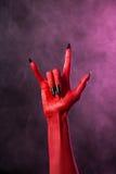 Rockowy znak, czerwonego diabła ręka z czarnymi gwoździami Obrazy Stock