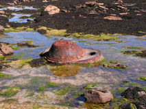 Rockpool Junk. A large piece of scrap metal in a rockpool causing pollution Royalty Free Stock Photography