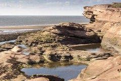 Rockpools und Klippe in Hilbre-Insel, Wirral, England Stockfotografie