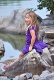 On The Rocks. Pretty litrle girl sitting on the rocks looking off into the lake Royalty Free Stock Photography