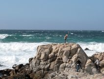 On the Rocks. Waves crashing into rocks on Monterey Bay with people standing on the rocks Royalty Free Stock Image