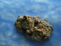 Rocks. A colorful rock in the water at dusk royalty free stock image