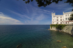 Rocks, Adriatic Sea  and Miramare Castle Royalty Free Stock Images