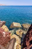 Rocks against a blue colored ocean, santorini island, greece stock photography