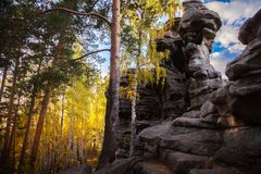 Rocks against the blue sky and forest stock photography