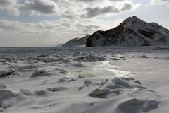 The rocks along the shore of a frozen sea Royalty Free Stock Images