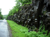 Rocks alongside road. Wet rock formation receding into distance alongside countryside road Stock Image
