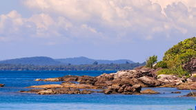 Rocks in Azure Sea by Beach with Plants against Bay Hills Sky stock footage
