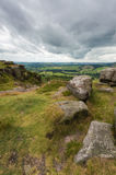 Rocks at Baslow Edge and the View Beyond. Some rocks on the edge of a hill at Baslow Edge with the countryside view beyond, in the Peak district, Derbyshire Royalty Free Stock Photography