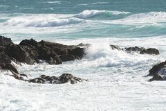 Rocks battered by waves in sea Royalty Free Stock Image