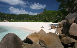 Rocks on the beach. Seychelles, La Digue, beach with lots of granite rocks, dark blue sky, partly cloudy, clear water, green palm trees and bushes Stock Photos