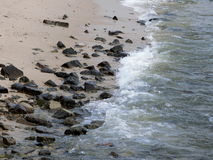 Rocks on the beach. Hong Kong - July 2016 Image shows a scattering of rocks of different sizes on the beach at Cheung Chau Island in Hong Kong with the waves Royalty Free Stock Photos