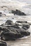 Rocks at the beach near Kingsburgh, KZN South Coast, near Durban, South Africa. Waves wash over the black rocks and sand at a beach near Kingsburgh on the KZN Stock Image