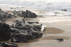 Rocks at the beach near Kingsburgh, KZN South Coast, near Durban, South Africa. Waves wash over the black rocks and sand at a beach near Kingsburgh on the KZN Stock Photos