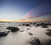 Rocks on the beach with red clouds Stock Image