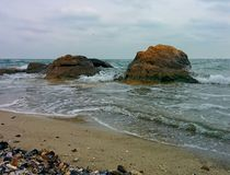 Rocks on beach. Rocks, shells  and waves on sand beach Royalty Free Stock Photos