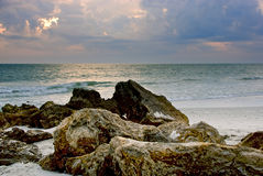 Rocks on the beach at sunset. Craggy rocks and boulders on the beach lead the viewers eye into this beautiful sunset image of florida's naples beach in the gulf stock photos