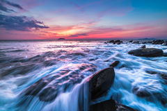 The rocks at the beach during sunset. Motion blur, soft focus du Stock Images