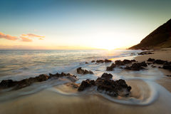 Rocks on the beach at Twilight. Ocean waves and rocks mingle at twilight on a secluded beach Stock Photo