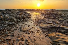 Rocks and beach uncovered in low tide with boats stock photos