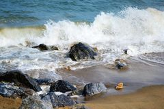 Beach waves. Rocks on the beach with waves smashed on them stock photography