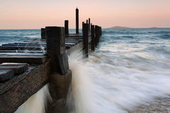 Rocks on the beach and wooden pier Stock Image