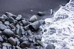 Rocks on the black sand and sea waves Stock Photography