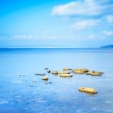Rocks in a blue ocean in a sea bay. Punta Ala, Tuscany, Italy Stock Image