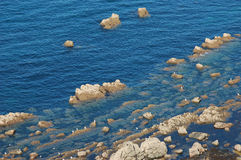 Rocks in the blue sea Stock Photos