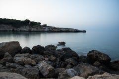 Rocks at the blurred sea water. Long exposure Stock Image