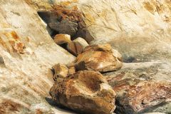 Closeup of rocks and boulders at the base of a sandstone cliff. Rocks and boulders gather where they have fallen at the base of a sandstone cliff where they once royalty free stock photo