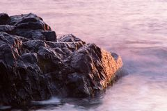 Rocks calm sea sunrise. Rocks and calm sea at sunset or sunrise with purple color of water in marine or nautical background Royalty Free Stock Images