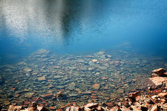 Rocks in clear water. Clear mountain lake with rocks at the edge Stock Photo