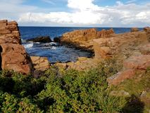 Rocks and cliffs by the sea, Hovs Hallar, Sweden, a cloudy day in August. Reddish cliffs and rocks steeping down into the blue sea. Dogrose bushes up front Royalty Free Stock Photos